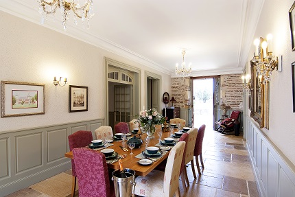dining table set out for fine dining in the Chateau with doors open to the river